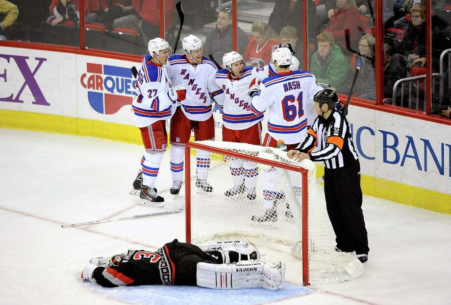 RALEIGH, NC - MARCH 07:  Teammates celebrate with Derek Stepan #21 of the New York Rangers after his game-winning goal against Anton Khudobin #31 of the Carolina Hurricanes during the third period of their game at PNC Arena on March 7, 2014 in Raleigh, North Carolina. The Rangers won 4-2.  (Photo by Grant Halverson/Getty Images) ORG XMIT: 181114319 Photo: Grant Halverson / 2014 Getty Images