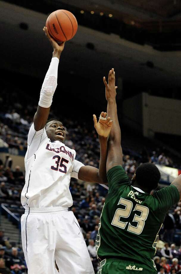 Connecticut's Amida Brimah, left, shoots over South Florida's Chris Perry, right, during the second half of an NCAA college basketball game on Wednesday, Feb. 12, 2014, in Hartford, Conn. Connecticut won 83-40. (AP Photo/Jessica Hill) Photo: Jessica Hill, Associated Press / Associated Press