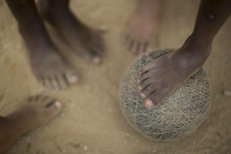 Barefoot playerskick a soccer ball that's seen better days in the Sao Carlos slum of Rio de Janeiro. Photo: Felipe Dana, Associated Press