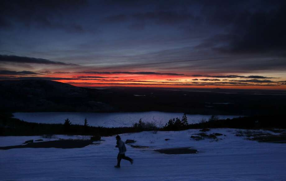 High above frozen Eagle Lake, a runner races in the fading daylight down from the 