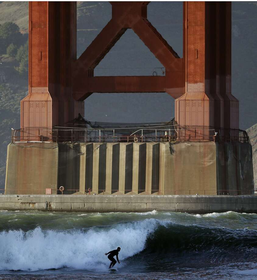 Gate crasher: A breaking wave gives a surfer a nice ride under the Golden Gate Bridge in San 