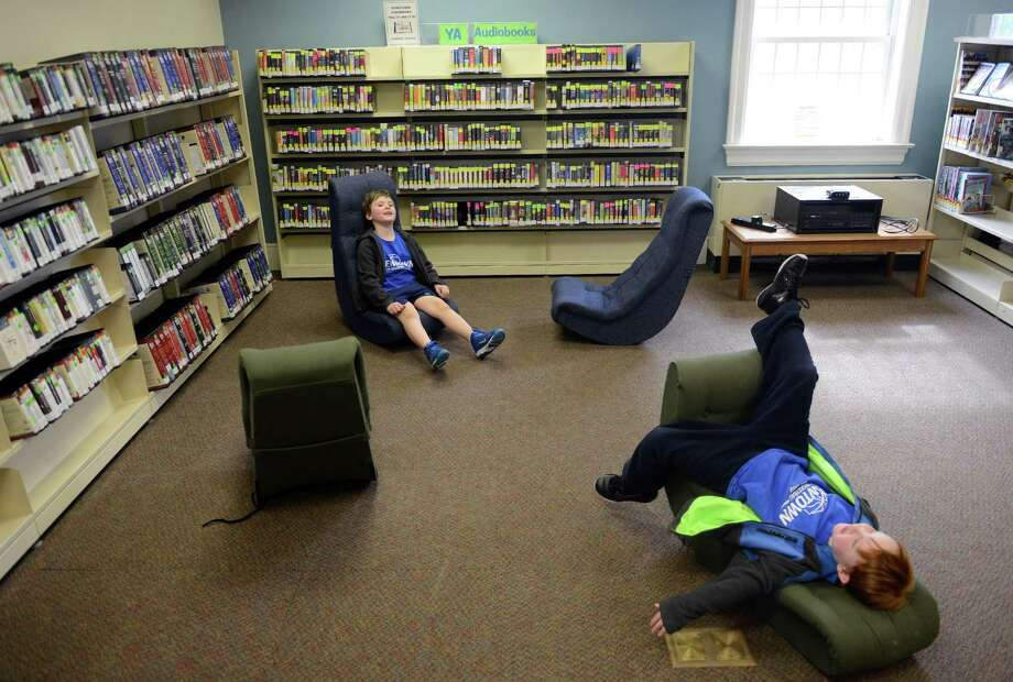 Brothers Charlie, left, and Marty Dunn, 6, of Sandy Hook, lounge on reclining chairs in the young adult section during the re-opening of the C.H. Booth Library in Newtown, Conn. Saturday, March 8, 2014.  The library was closed for 8 weeks after a frozen sprinkler pipe burst, causing extensive flood damage throughout the library. Photo: Tyler Sizemore / The News-Times