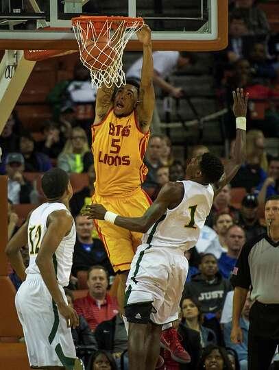 Yates' JC Washington (5) dunks the ball past Dallas Madison's Johnathan Turner.