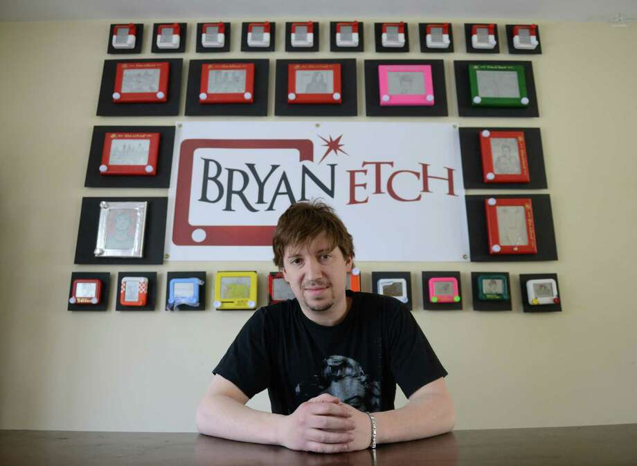 Etch-a-Sketch artist Bryan Madden poses in front of a collection of his work in his home in Danbury, Conn. Saturday, March 8, 2014.  Madden began sketching in college and decided to take it up professionally after getting a positive reponse from viewers on the Internet.  The work is preserved by removing the sand and aluminum powder after the piece is completed. Photo: Tyler Sizemore / The News-Times