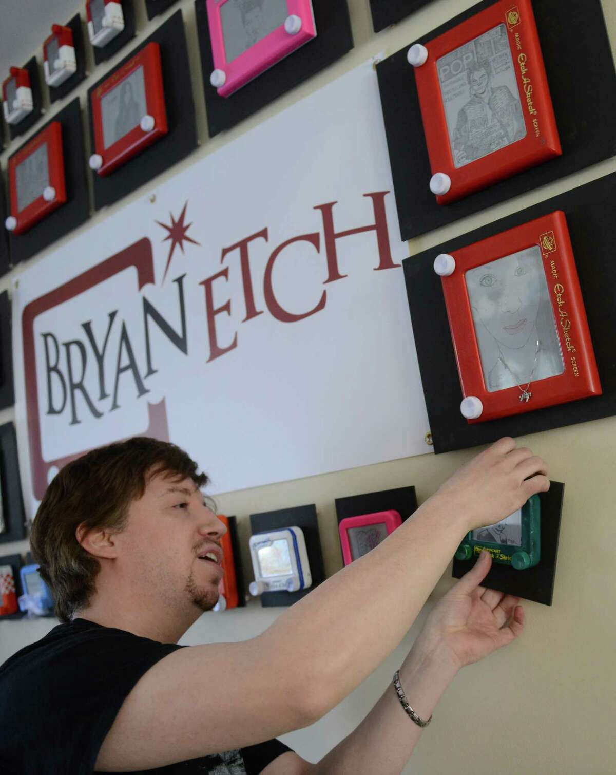 Etch-a-Sketch artist Bryan Madden hangs a new piece on the wall in his home in Danbury, Conn. Saturday, March 8, 2014. Madden began sketching in college and decided to take it up professionally after getting a positive reponse from viewers on the Internet. The work is preserved by removing the sand and aluminum powder after the piece is completed.