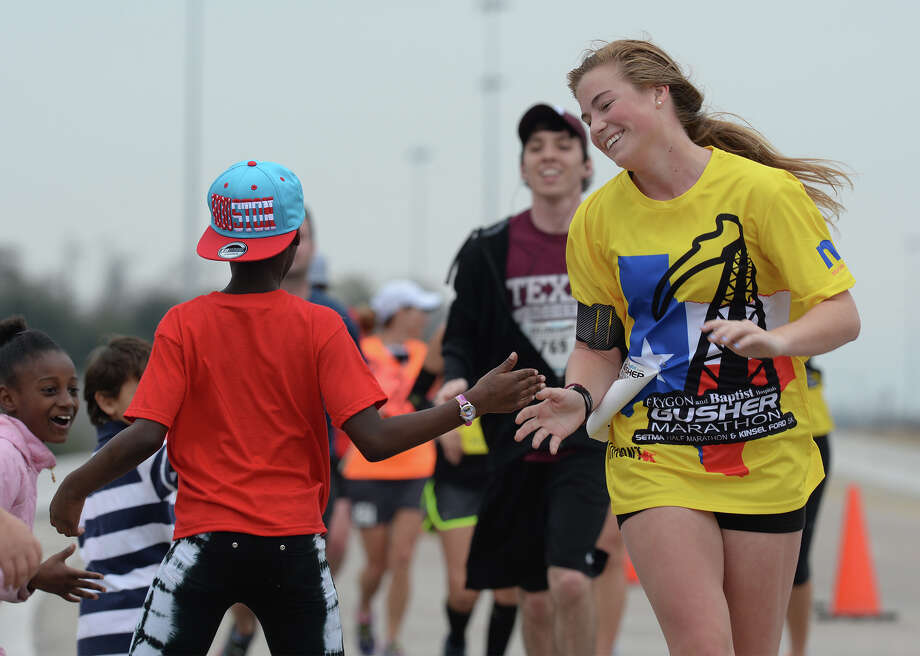 A group of children high five marathoners and half marathoners along Martin Luther King Parkway during the Gusher Marathon on Saturday. Photo taken Saturday, March 08, 2014 Guiseppe Barranco/@spotnewsshooter Photo: Guiseppe Barranco, Photo Editor