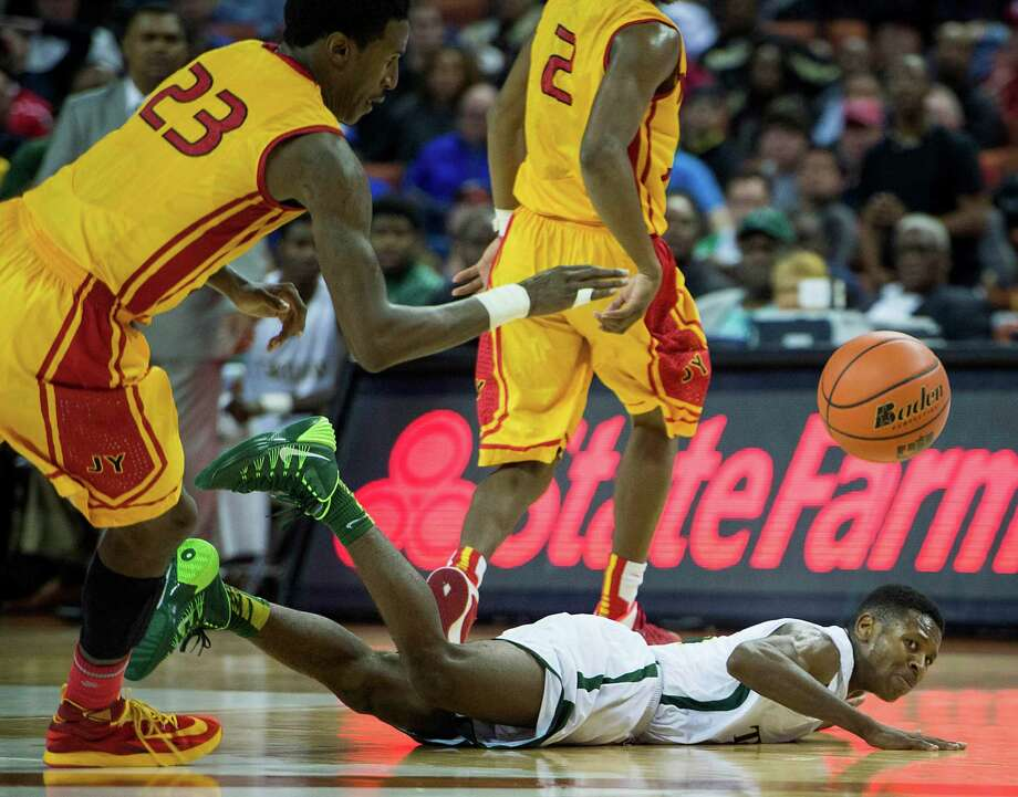 Madison guard Cameron Bryant hits the floor chasing a loose ball against Yates' Melvin Swift. Photo: Smiley N. Pool, Houston Chronicle / © 2014  Houston Chronicle
