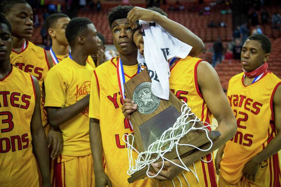 Yates guard Jacob Young is consoled by teammate Darius Hill as he holds the second place trophy. Photo: Smiley N. Pool, Houston Chronicle / © 2014  Houston Chronicle