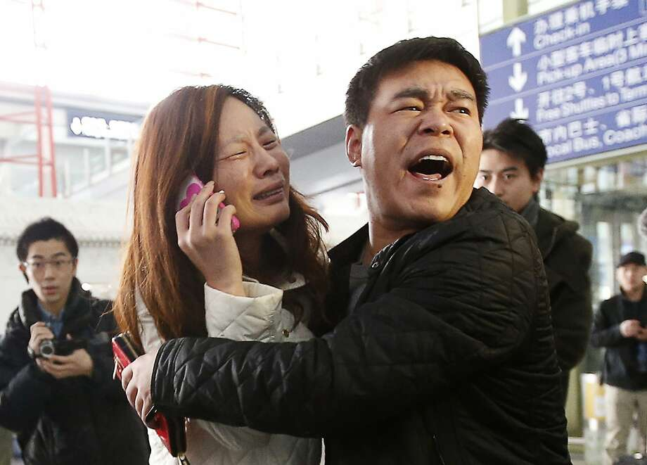A relative of a passenger on a Malaysia Airlines plane, which disappeared with 239 people aboard, talks on her mobile phone at the Beijing Capital International Airport. Photo: Kim Kyung-hoon, Reuters