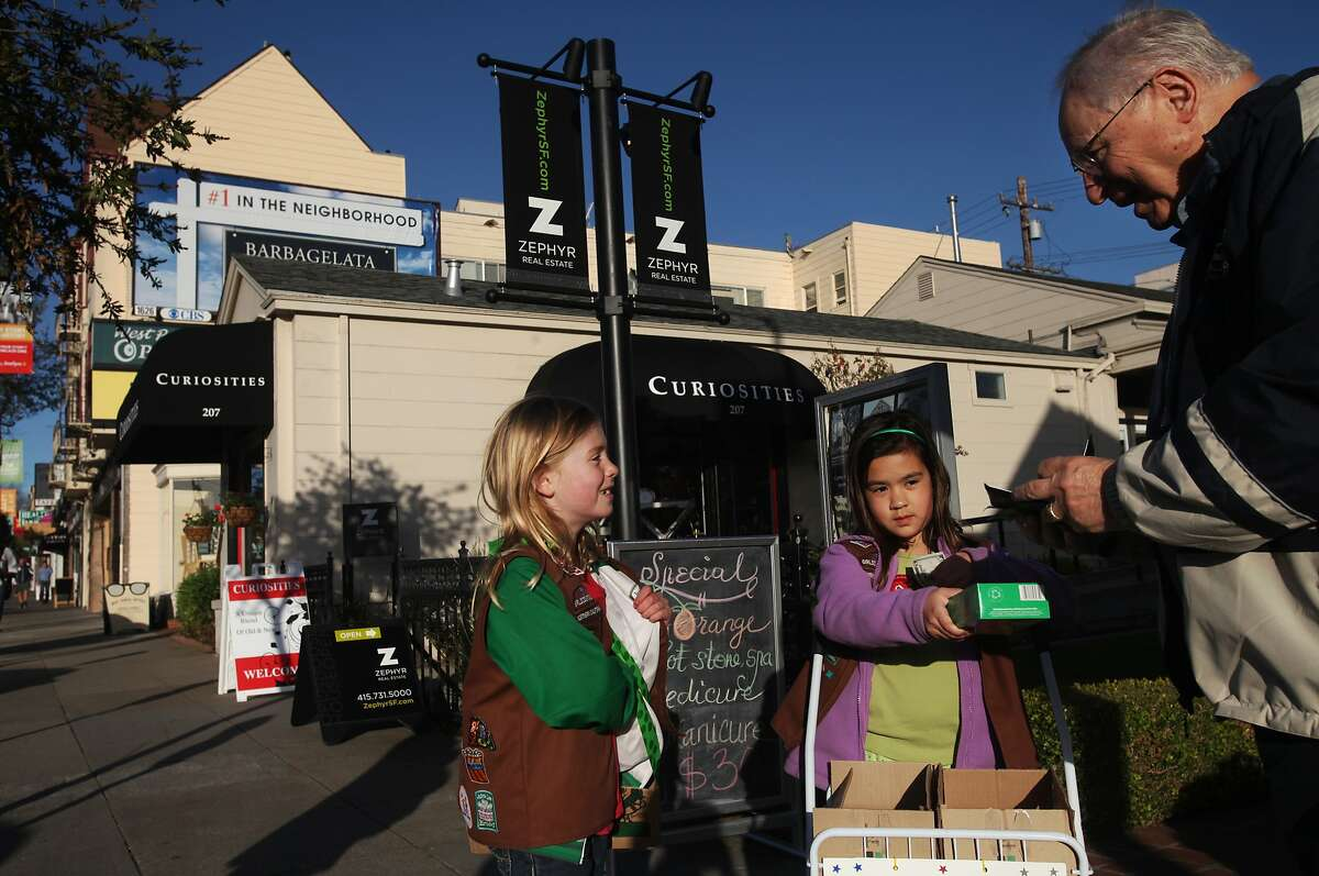 Paul Kameny buys Girl Scout cookies from Meghan Sheehan, 8, left, and Charlotte Jiggens, 7, March 7, 2014 on West Portal Ave. in San Francisco, Calif. Amy Nachman, who has been living in the neighborhood for 12 years loves it,