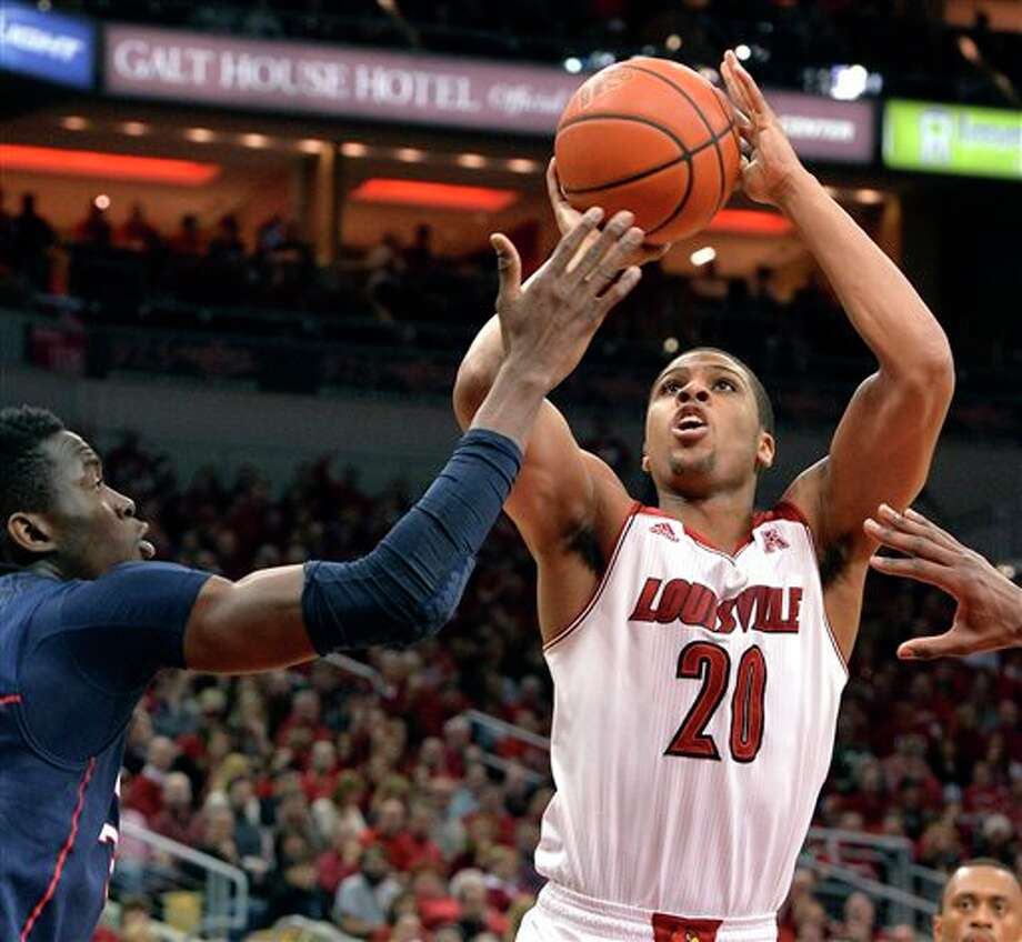 Louisville's Wayne Blackshear  shoots as Connecticut's Amida Brimah defends during the second half of  an NCAA college basketball game, Saturday, March 8, 2014, in Louisville,  Ky. Louisville defeated UConn 81-48. (AP Photo/Timothy D. Easley)