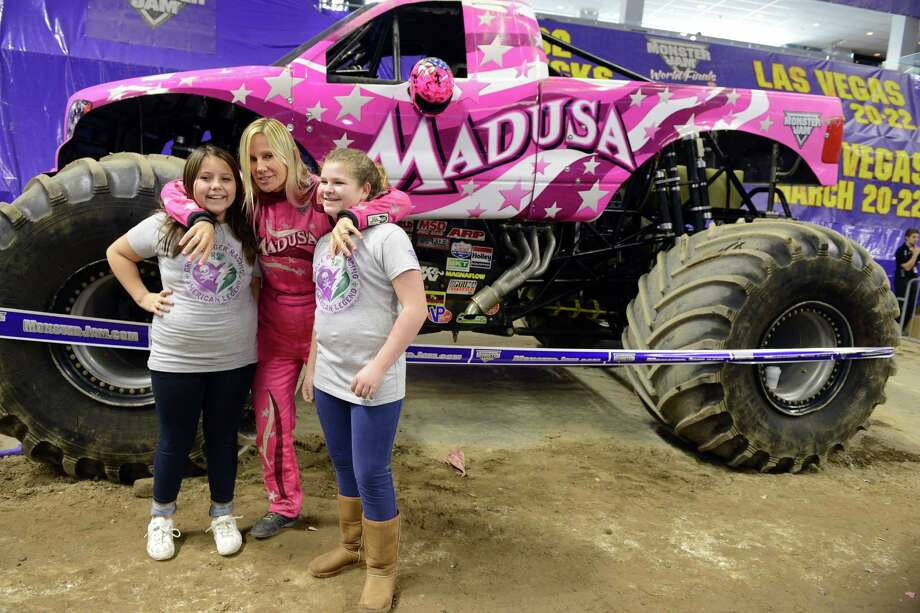 Madusa, driver Debrah Miceli, poses for a photo with fans Jasmine Guerrero, 11, of Bethel, and Samantha Barnum, 12, of Bethel, during the Monster Jam pit party Saturday, Mar. 8, 2014, at the Webster Bank Arena in Bridgeport, Conn. The last show is Sunday, March 9 at 2 p.m. proceeded by the pit party at 11 a.m. Photo: Autumn Driscoll / Connecticut Post