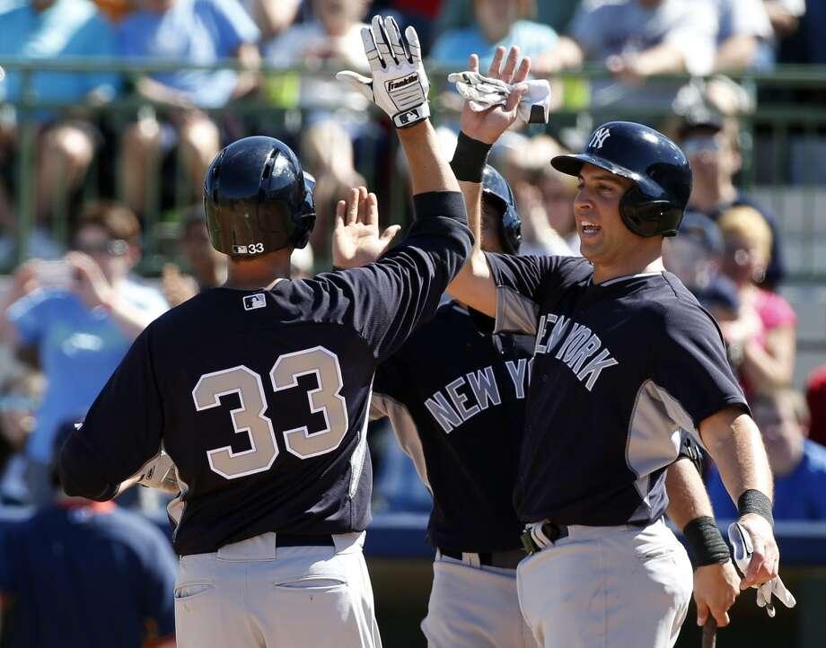 Yankees teammates congratulate Kelly Johnson on his two-run home run against the Astros. Photo: Alex Brandon, Associated Press