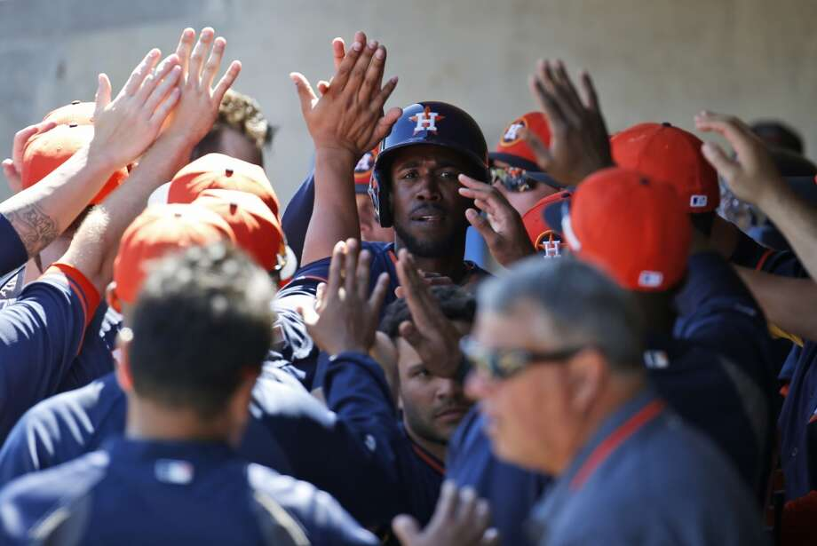 Dexter Fowler of the Astros receives kudos after scoring in the first inning. Photo: Alex Brandon, Associated Press