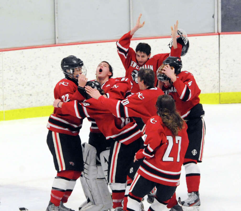 New Canaan goalie MacLean Wright, second from left, screams as he is surrounded by teammates at the conclusion of a 5-2 victory over Darien as New Canaan won the FCIAC boys hockey championship game at Terry Conners Rink in Stamford, Saturday, March 8, 2014. New Canaan players are Pat Hompe (#22), left, James Franzis (#20) and Cooper Manchuck (#27), bottom right. Wright was named the MVP. Photo: Bob Luckey / Greenwich Time