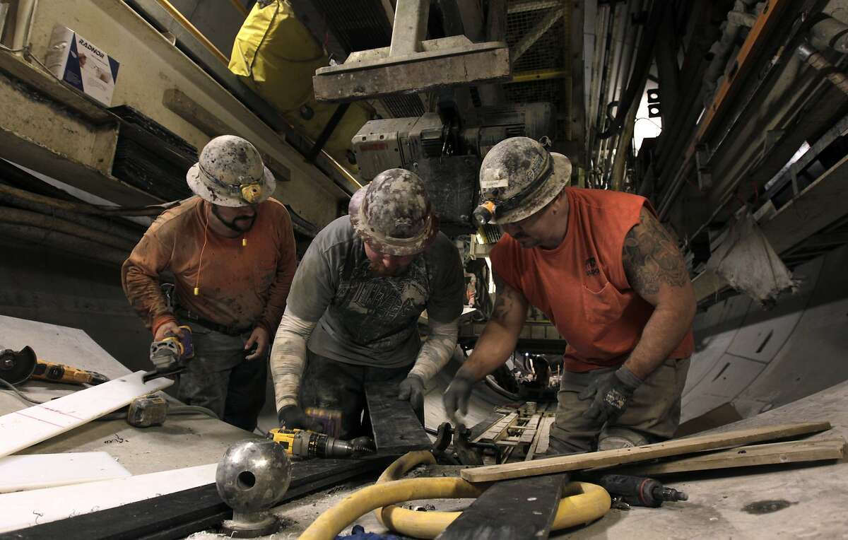 Construction workers prepare a section of curved retaining wall for installation inside the northbound tunnel of Muni's Central Subway project in San Francisco, Calif. on Saturday, March 8, 2014. Two large boring machines, Big Alma and Mom Chung, are grinding their way north from Fourth and Bryant streets towards Chinatown and North Beach.