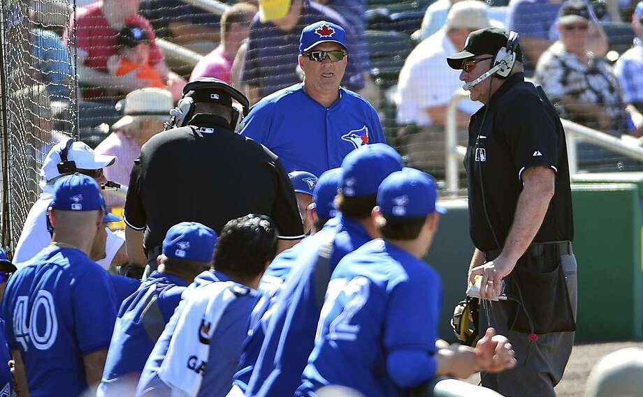 The Blue Jays wait while umpires get a decision from the replay official after a challenge. Photo: Tommy Gilligan, Reuters