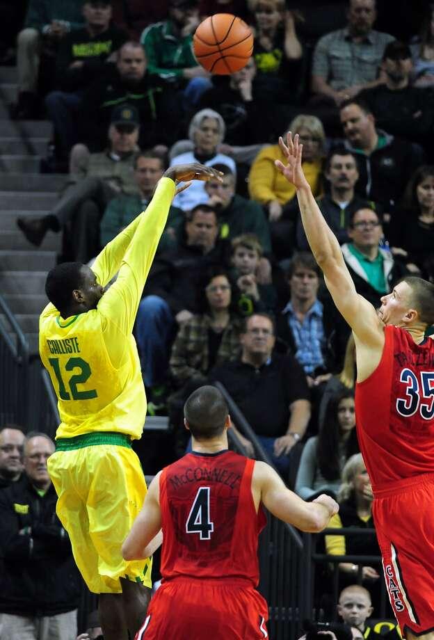 Oregon's Jason Calliste hits a big three-point shot over Arizona's Kaleb Tarczewski in the second half. Photo: Steve Dykes, Getty Images