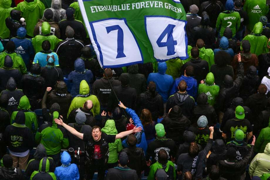 Seattle Sounders fans cheer for their team during the season opener against Sporting KC on Saturday, March 8, 2014 at CenturyLink Field. The Sounders defeated Kansas City 1-0. (Joshua Trujillo, seattlepi.com) Photo: SEATTLEPI.COM