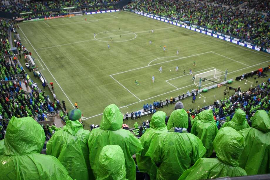 Seattle Sounders fans try to keep dry as they watch action against Sporting KC during the Sounders season opener on Saturday, March 8, 2014 at CenturyLink Field. The Seattle Sounders defeated Kansas City 1-0. (Joshua Trujillo, seattlepi.com) Photo: JOSHUA TRUJILLO, SEATTLEPI.COM