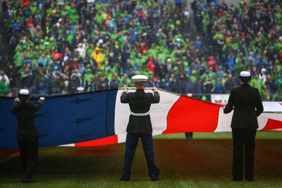 Members of the U.S. military hold the flag during the Sounders season opener on Saturday, March 8, 2014 at CenturyLink Field. The Sounders defeated Kansas City 1-0. (Joshua Trujillo, seattlepi.com) Photo: SEATTLEPI.COM