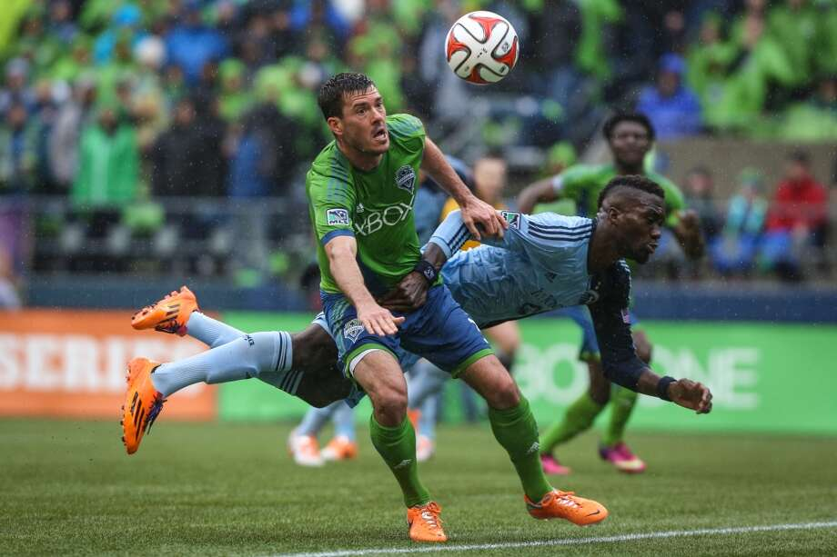 Seattle Sounders player Brad Evans and Sporting KC player C.J. Sapong tangle for control of the ball near the goal during the Sounders season opener on Saturday, March 8, 2014at CenturyLink Field. The Sounders defeated Kansas City 1-0. (Joshua Trujillo, seattlepi.com) Photo: SEATTLEPI.COM