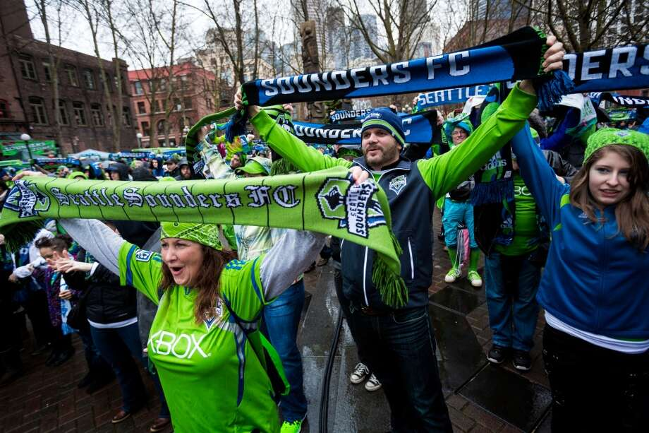 "Sounders FC fans raise their scarves at the ""March to Match"" before the season home opener against Sporting KC Saturday, March 8, 2014, in Seattle. (Jordan Stead, seattlepi.com) Photo: SEATTLEPI.COM"