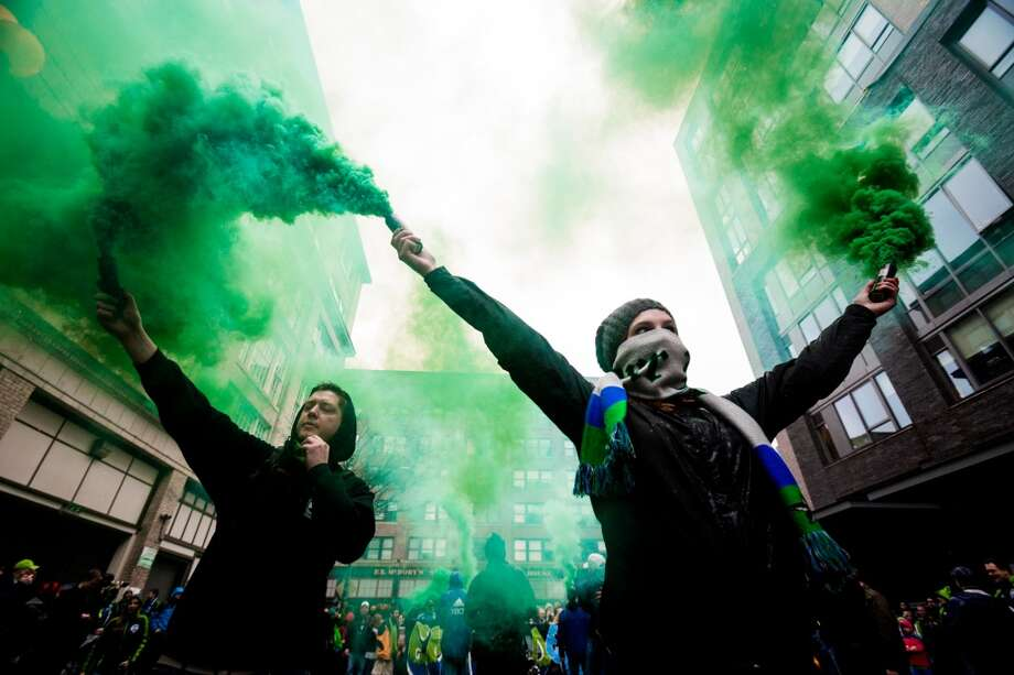 "Green clouds fill the air as Sounders FC fans set off some smoke bombs streets from Occidental Park to CenturyLink Field for the ""March to Match"" before the season home opener against Sporting KC Saturday, March 8, 2014, in Seattle. (Jordan Stead, seattlepi.com) Photo: SEATTLEPI.COM"