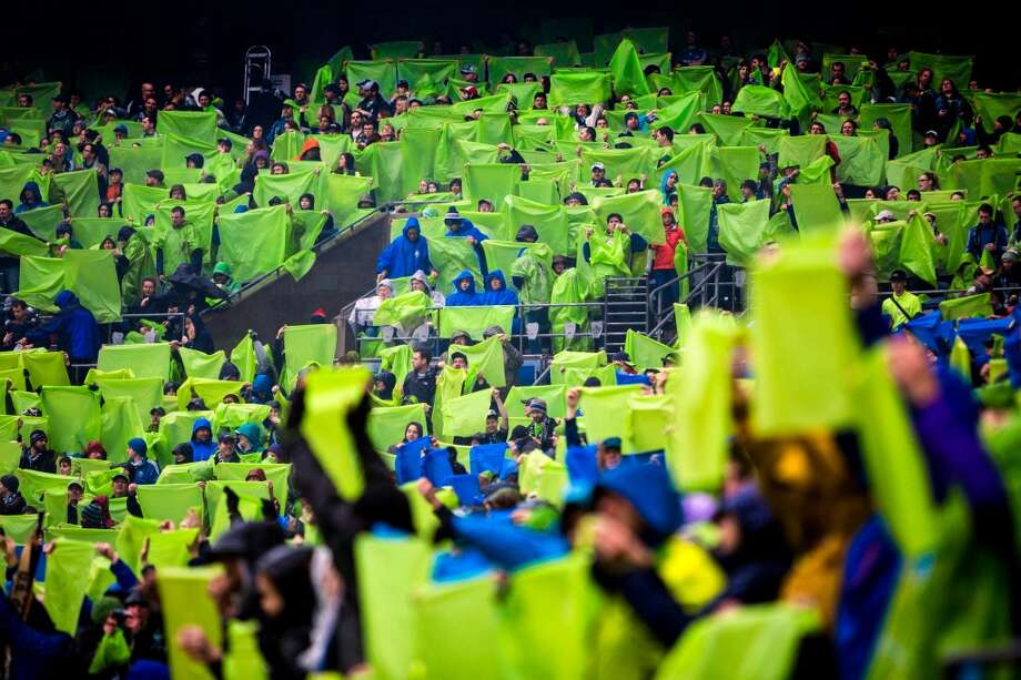 Sounders FC fans hoist the plastic of their complementary rain coverings before season home opener against Sporting KC Saturday, March 8, 2014, at CenturyLink Field in Seattle. The Sounders beat Sporting KC 1-0 in the final moments of stoppage time. (Jordan Stead, seattlepi.com) Photo: SEATTLEPI.COM
