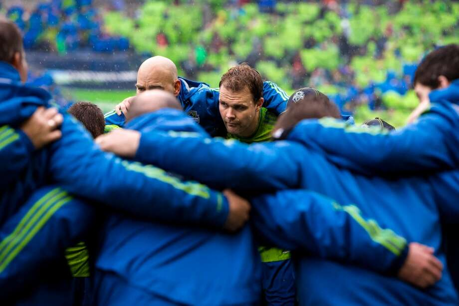 Sounders FC players and coaches huddle up under driving rain before the season home opener against Sporting KC Saturday, March 8, 2014, at CenturyLink Field in Seattle. The Sounders beat Sporting KC 1-0 in the final moments of stoppage time. (Jordan Stead, seattlepi.com) Photo: SEATTLEPI.COM