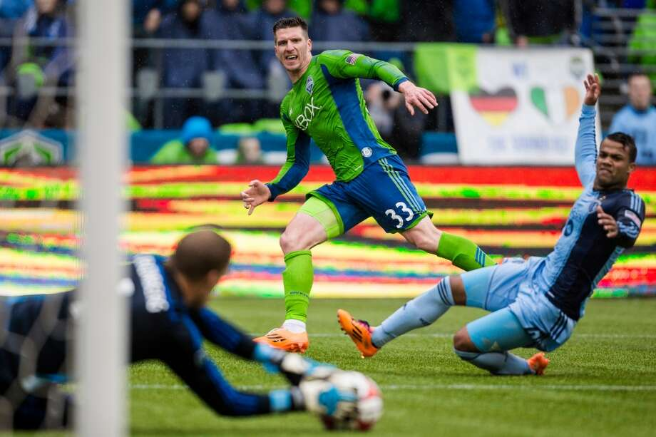 Sounders FC forward Kenny Cooper, center, watches his missed shot get nabbed by Sporting KC goalkeeper Eric Kronberg, left, during the season home opener Saturday, March 8, 2014, at CenturyLink Field in Seattle. The Sounders beat Sporting KC 1-0 in the final moments of stoppage time. (Jordan Stead, seattlepi.com) Photo: SEATTLEPI.COM