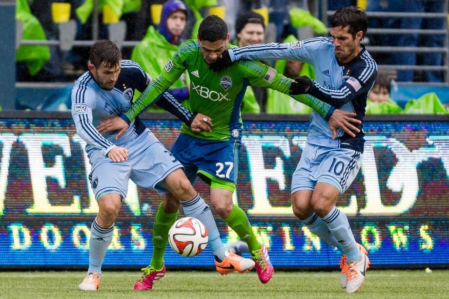 Sounders FC midfielder Lamar Neagle, center, pushes through opposing players while fighting for ball control during the season home opener against Sporting KC Saturday, March 8, 2014, at CenturyLink Field in Seattle. The Sounders beat Sporting KC 1-0 in the final moments of stoppage time. (Jordan Stead, seattlepi.com) Photo: SEATTLEPI.COM