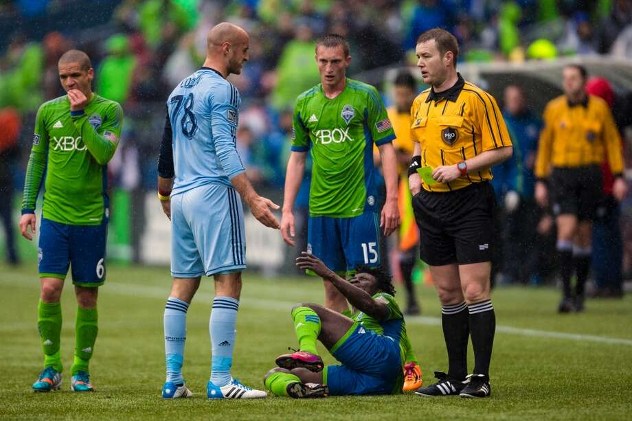 Sporting KC defender Aurelien Collin, center left, reacts to a yellow card pulled on him after knocking over Obafemi Martins, bottom, during the season home opener Saturday, March 8, 2014, at CenturyLink Field in Seattle. The Sounders beat Sporting KC 1-0 in the final moments of stoppage time. (Jordan Stead, seattlepi.com) Photo: SEATTLEPI.COM
