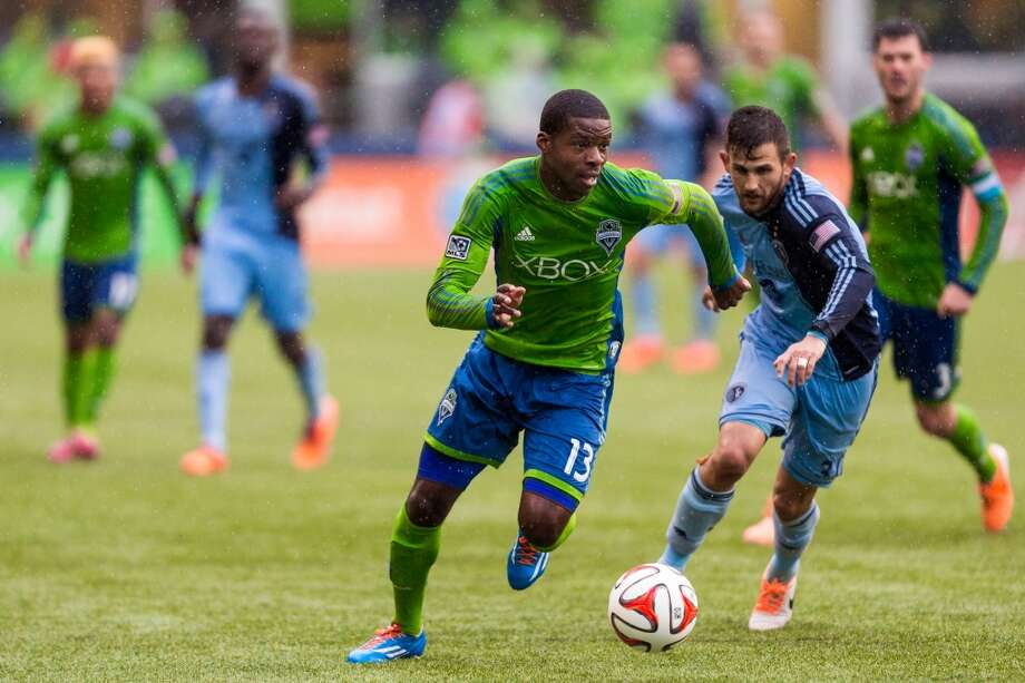 Sounders FC Sean Okoli, center, dribbles downfield during the season home opener against Sporting KC Saturday, March 8, 2014, at CenturyLink Field in Seattle. The Sounders beat Sporting KC 1-0 in the final moments of stoppage time. (Jordan Stead, seattlepi.com) Photo: SEATTLEPI.COM