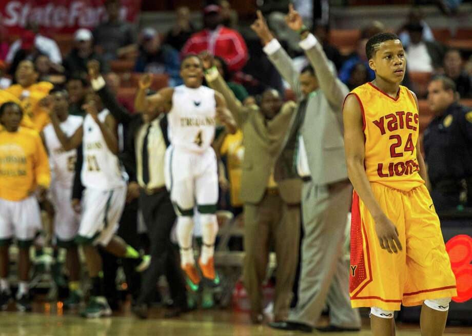 Yates guard Jacob Young walks away as the Dallas Madison bench erupts at the final buzzer of the the boys' UIL Class 3A state basketball championship game. Photo: Smiley N. Pool, Houston Chronicle / © 2014  Houston Chronicle