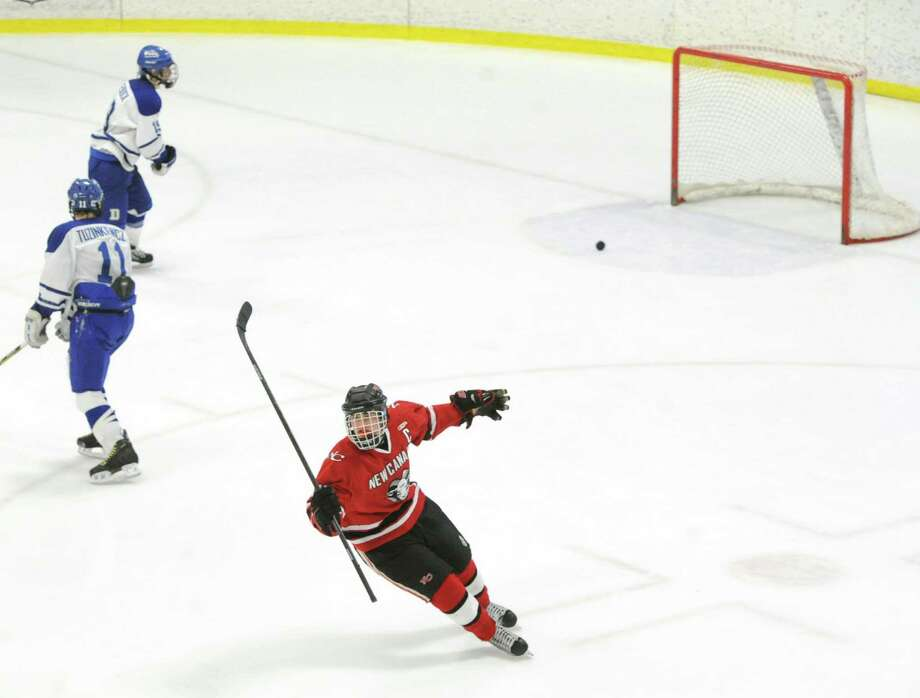 Below, New Canaan's John O'Rourke (#11) celebrates his empty-net 3rd period goal making the score 5-2 during the FCIAC boys hockey championship game between New Canaan High School and Darien High School at Terry Conners Rink in Stamford, Saturday, March 8, 2014. New Canaan defeated Darien, 5-2, to take the title and New Canaan goalie MacLean Wright was named the MVP. Photo: Bob Luckey / Greenwich Time