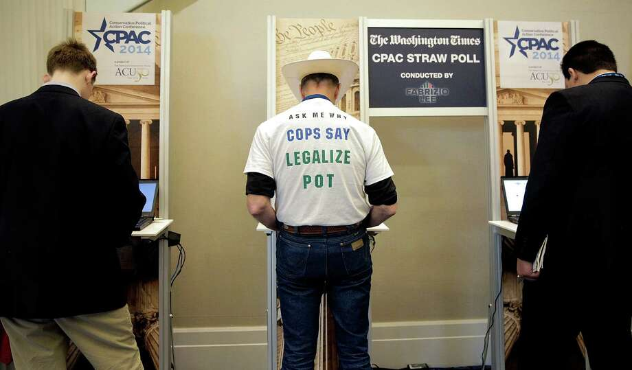 Attendees stand at computers to cast their vote in the presidential straw poll during the 41st annual Conservative Political Action Conference in National Harbor, Md. Photo: T.J. Kirkpatrick / Getty Images / 2014 Getty Images