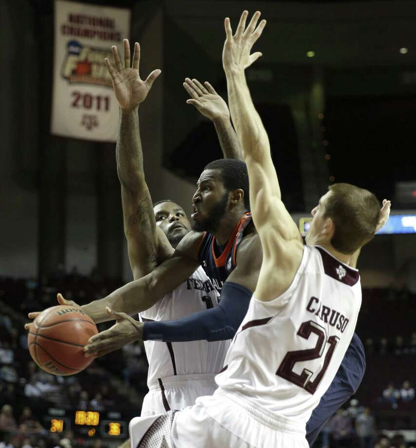 Auburn's KT Harrell, who led the Tigers with 20 points, slips a pass between Texas A&M defenders Alex Caruso (right) and Kourtney Roberson in the second half. Photo: David J. Phillip / Associated Press / AP