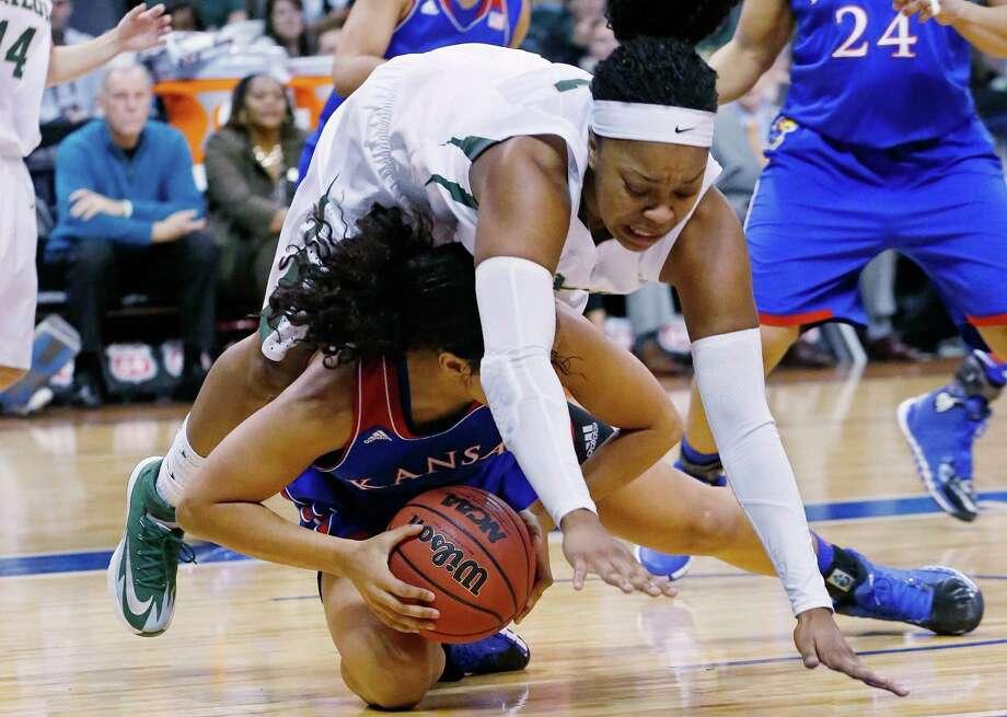 Baylor's Odyssey Sims tumbles over Kansas' Dakota Gonzalez in the second half of Saturday's Big 12 women's quarterfinal game in Oklahoma City. Photo: Sue Ogrocki, STF / AP