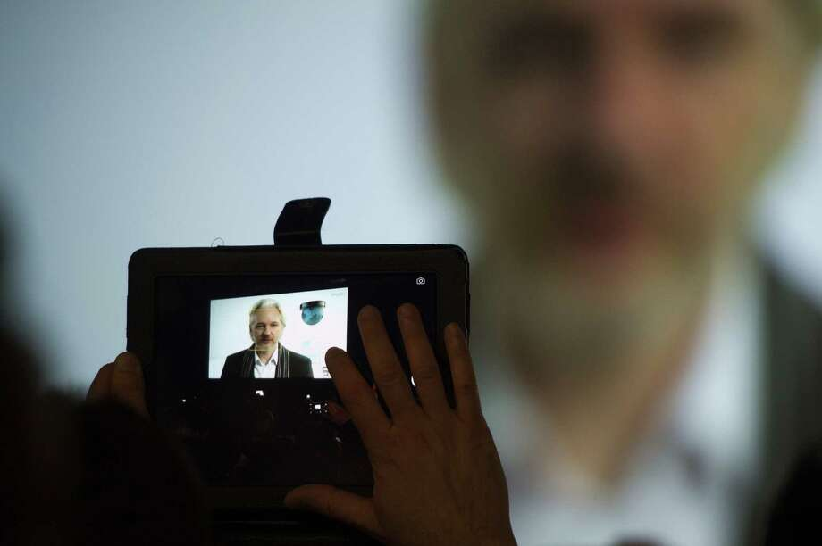 A South By Southwest Interactive attendee uses a mobile device to take a photograph of WikiLeaks founder Julian Assange as he speaks via Skype during a panel discussion. Photo: David Paul Morris / Bloomberg News / © 2014 Bloomberg Finance LP