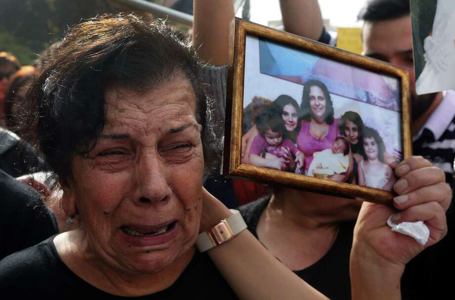 A mother carries a picture of her slain daughter while taking part in a rally demanding that parliament approve a law that protects women from domestic violence in Beirut. Photo: Bilal Hussein / Associated Press / AP