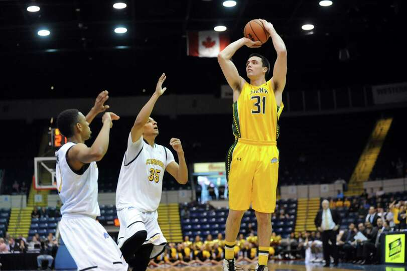 Siena's Brett Bisping, right, shoots for three points as Canisius' Zach Lewis, left, and Jordan Heat