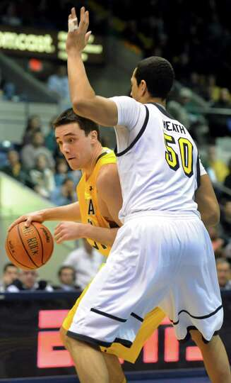 Siena's Brett Bisping, left, drives around Canisius' Josiah Heath in their second-round basketball g