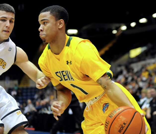 Siena's Marquis Wright, right, drives around Canisius' Billy Baron in their second-round basketball