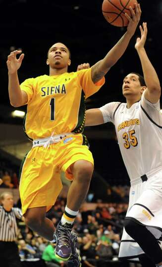 Siena's Marquis Wright, left, goes to the hoop as Canisius' Jordan Heath defends in their second-rou