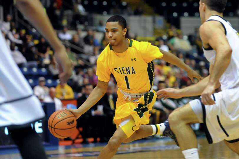 Siena's Marquis Wright, center, drives up court in their second-round basketball game of the MAAC To