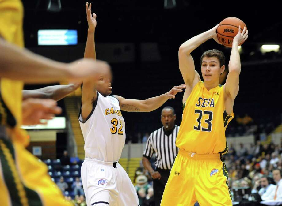 Siena's Rob Poole, right, looks to pass as Canisius' Dominique Raney defends in their second-round basketball game of the MAAC Tournament on Saturday, March 8, 2014, at MassMutual Center in Springfield, Mass. (Cindy Schultz / Times Union) Photo: Cindy Schultz / 00026001A