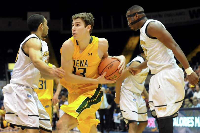 Siena's Rob Poole, center, charges for the hoop as Canisius' Chris Perez, left, and Chris Manhertz d