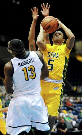 Siena's Evan Hymes, right, shoots for the hoop as Canisius' Chris Manhertz defends in their second-r