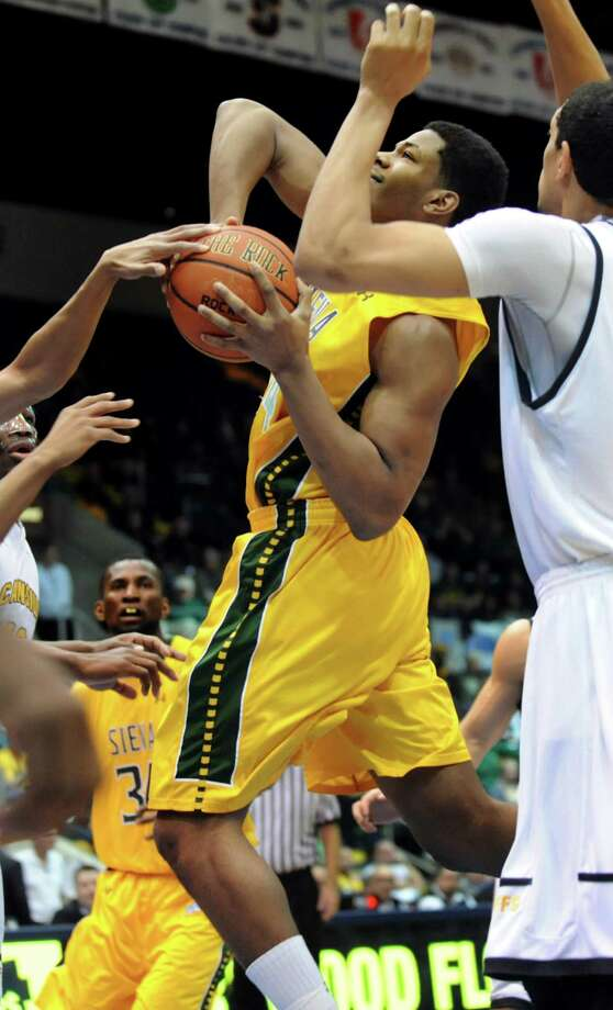 Siena's Lavon Long, center, runs into Canisius' defense as he aims for the hoop in their second-round basketball game of the MAAC Tournament on Saturday, March 8, 2014, at MassMutual Center in Springfield, Mass. (Cindy Schultz / Times Union) Photo: Cindy Schultz / 00026001A